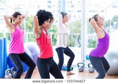 Women exercising with hands behind head in fitness studio