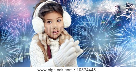 winter, holidays, children and people concept - happy little girl wearing earmuffs over firework background