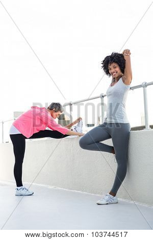 Portrait of happy young woman stretching while female friend exercising by railing