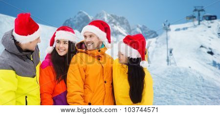 winter holidays, christmas, friendship and people concept - happy friends in santa hats and ski suits over downhill skiing and mountains background