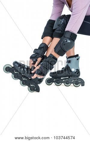 Low section of sporty woman wearing inline skates over white background