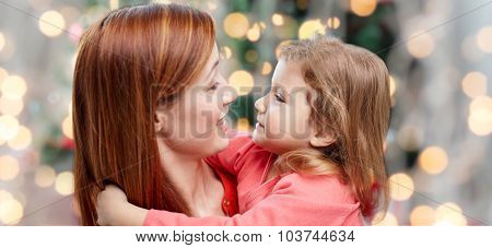 family, holidays, children and people concept - happy mother and little daughter hugging over christmas tree lights background