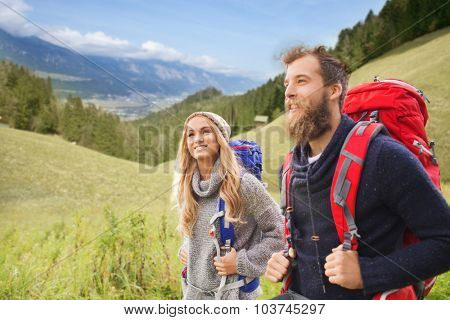 adventure, travel, tourism, hike and people concept - smiling couple walking with backpacks over natural landscape background