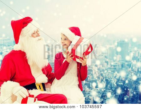 holidays, christmas, childhood and people concept - smiling little girl with santa claus and gifts over snowy city background