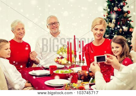 family, holidays, generation, christmas and people concept - smiling family having dinner and taking photo with camera at home