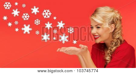 people, holidays, christmas and winter concept - lovely woman in red clothes sending snowflakes from on palms of her hands over red background