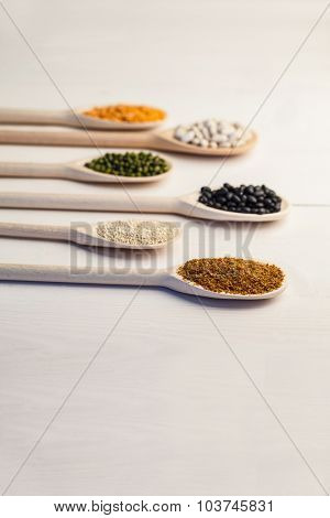 Wooden spoons of pulses and seeds on wooden table