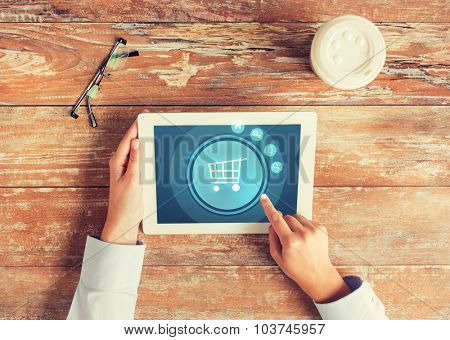 business, people, online shopping and technology concept - close up of hands pointing finger to tablet pc computer screen with trolley icon, coffee cup and eyeglasses on table