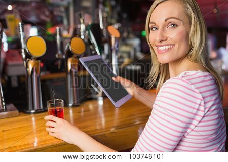 Portrait of woman with drink holding digital tablet at bar counter