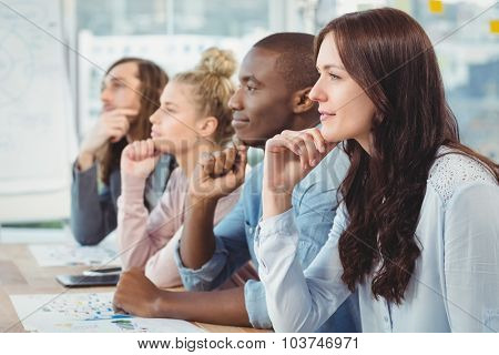 Thoughtful business people with hand on chin while sitting at desk in office