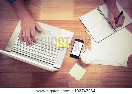 Cropped hand of businessman writing on spiral book while using laptop at desk in office
