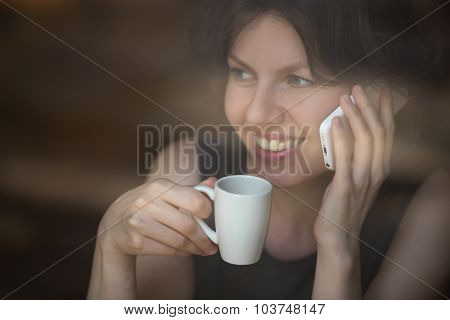 Young Woman On Mobile Phone In Cafe