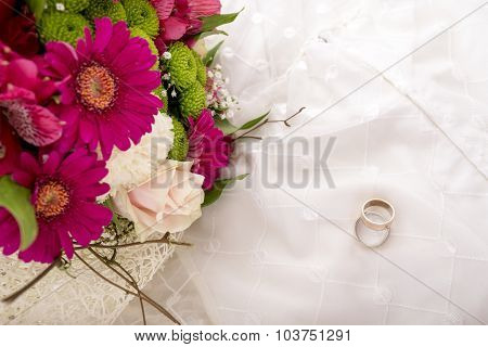 Wedding Setting - Top View Of Bride And Groom Rings And Beautiful Colourful Bouquet Of Flowers