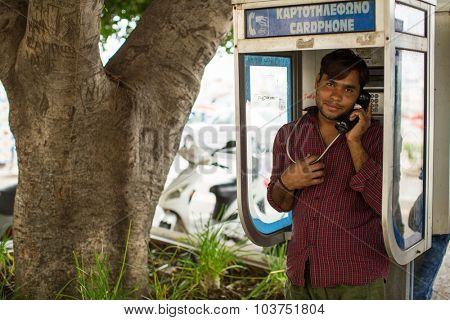KOS, GREECE - SEP 28, 2015: Refugee talking on a phone. Kos island is located just 4 km. from the Turkish coast, and many refugees come from Turkey in an inflatable boats.