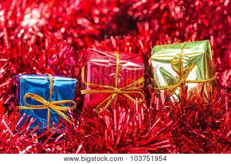 Three Gift Boxes On Red Tinsel