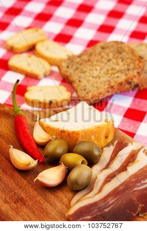 Traditional mediterranean food with ham, olives, hot peppers and bread. Shallow depth of field. Selective focus.