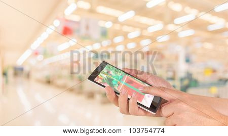 Male Hand Is Holding A Modern Touch Screen Phone And Blurred Image Of Supermarket.