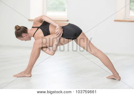 Full length portrait of a young woman doing stretching exercises in gym