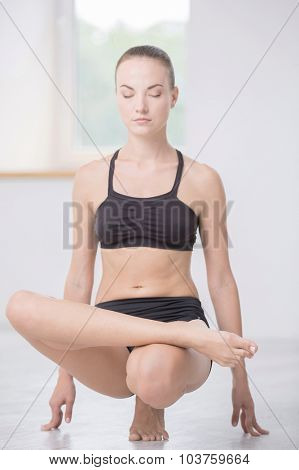 Full length portrait of pretty woman doing yoga exercises in gym