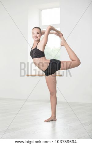 Full length portrait of a smiling woman doing yoga exercises in gym