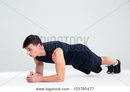 Portrait of a sports man doing elbow plank exercises isolated on a white background