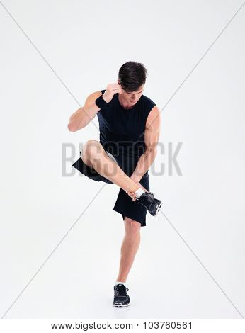 Full length portrait of a sports man doing warm up exercises isolated on a white background