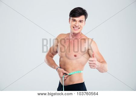 Portrait of a smiling fitness man measuring his body and showing thumb up isolated on a white background