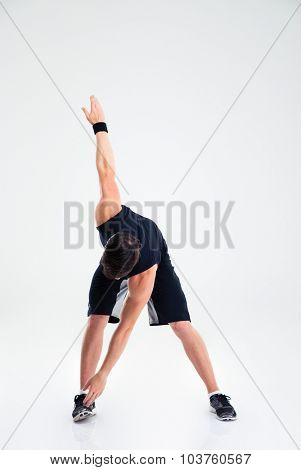Full length portrait of athletic man doing stretching exercises isolated on a white background