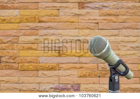 Microphone On A Stand With Blurred Wall Made From Yellow Sandstone Bricks, Copyspace.