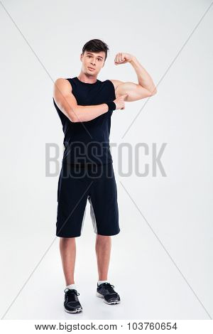 Full length portrait of a fitness man showing his biceps isolated on a white background