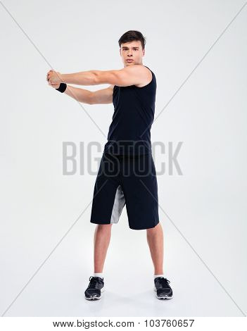 Full length portrait of a fitness man stretching hands isolated on a white background