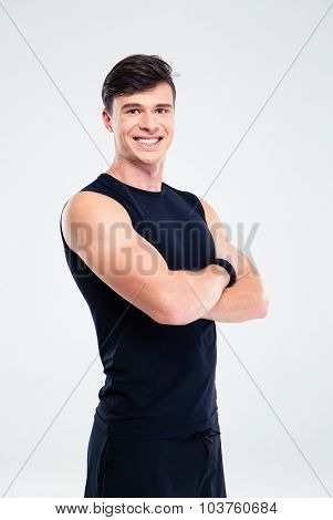 Portrait of a smiling sports man standing with arms folded isolated on a white background