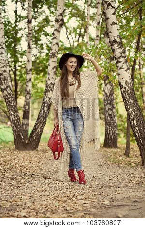 Full length portrait of a beautiful young woman in a hat and a red bag posing against a background of the autumn park