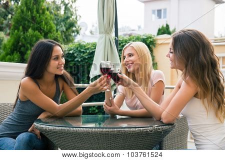 Portrait of a happy three girlfriends drinking red wine outdoors in the restaurant