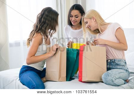 Portrait of a cheerful three girlfriends with many shopping bags at home