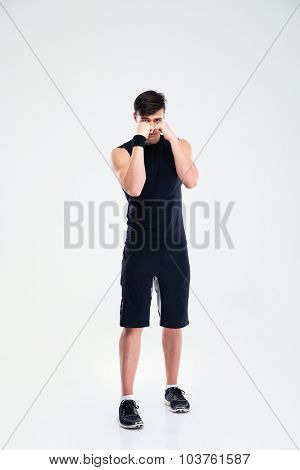 Full length portrait of a male boxer standing isolated on a white background