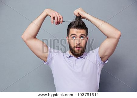Portrait of a funny man cutting his hair over gray background