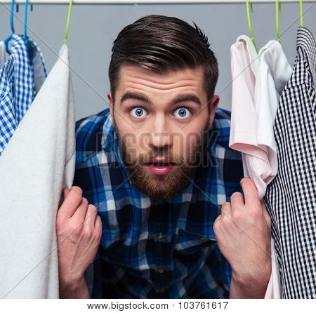 Portrait of a surprised hipster man standing near rack with clothes and looking at camera