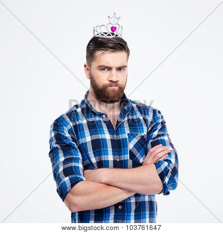 Portrait of a sad man in queen crown standing with arms folded isolated on a white background