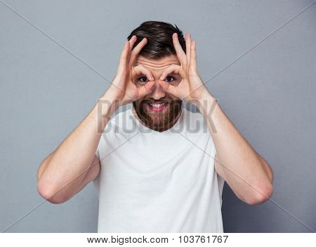 Portrait of a happy man looking at camera through fingers over gray background