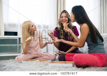 Portrait of a three happy girlfriends eating pizza at home