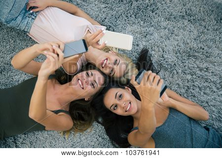 Top view portrait of a three girlfriends using smartphones on the carpet at home