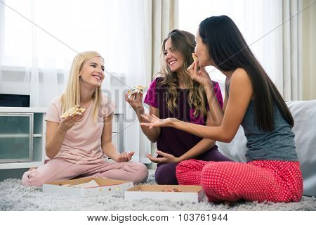 Portrait of a three beautiful girlfriends eating pizza at home