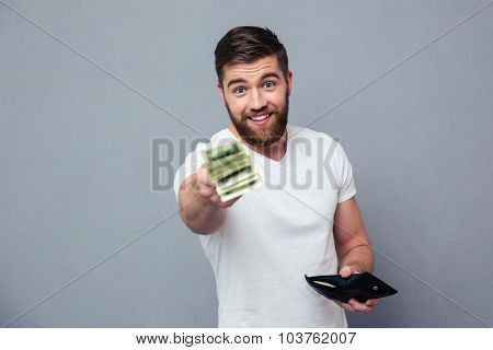 Portrait of a happy casual man giving money at camera over gray background