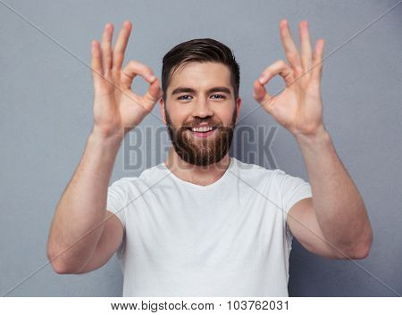 Portrait of a happy casual man showing ok sign with fingers over gray background