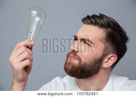 Portrait of a young man looking on bulb over gray backgorund