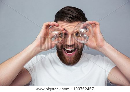 Portrait of a funny man looking at camera through bulb over gray background
