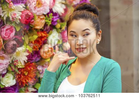 Beautiful asian woman making a call me gesture, indoor