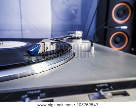 Close up view of old fashioned turntable playing a track from black vinyl with light bluish interior lightning