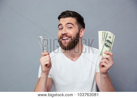 Portrait of a smiling man holding bulb and dollar bills over gray background